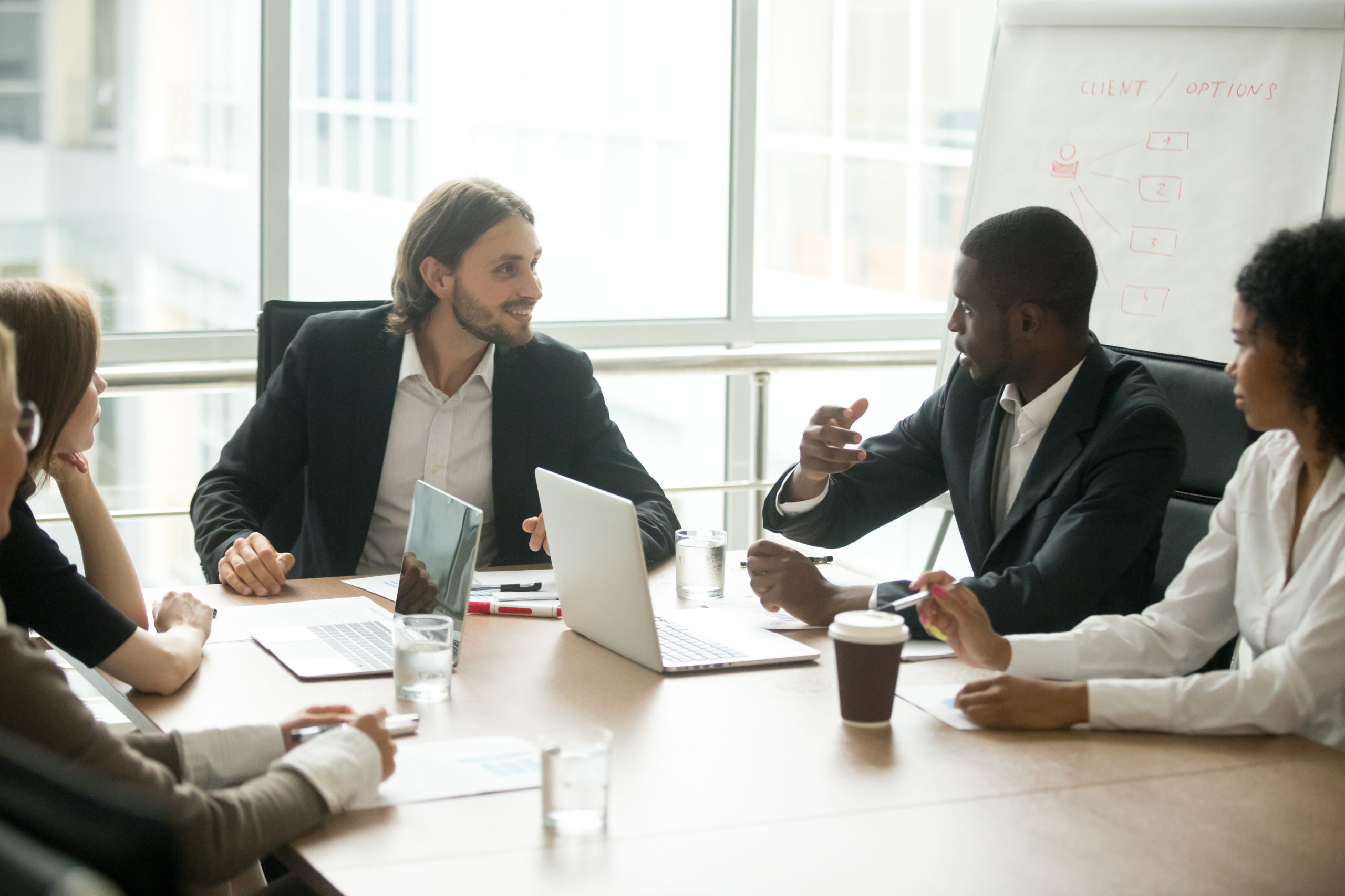Diverse business executives discussing project sitting at conference table, multiracial partners talking about marketing plan at corporate briefing, african manager offering new idea at group meeting